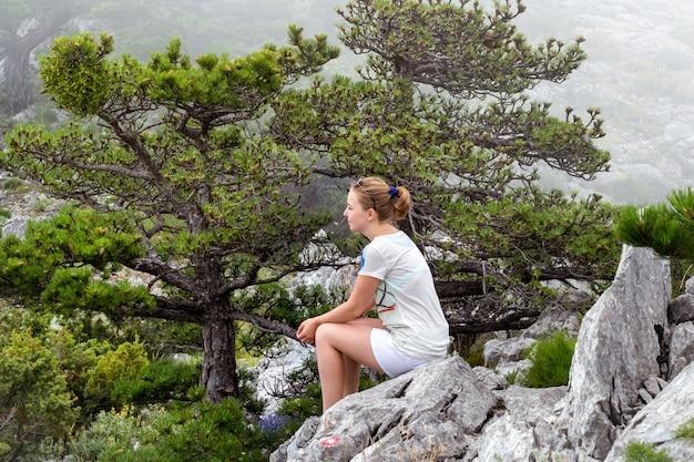 女の子は山のピークの岩の上に座る。