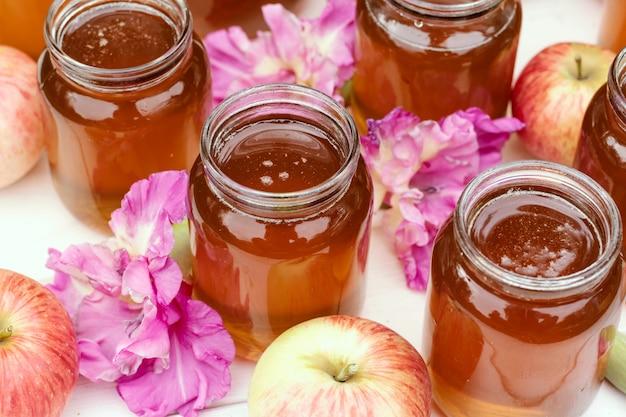 明るい白い木製の背景にガラスの瓶に新鮮な蜂蜜。