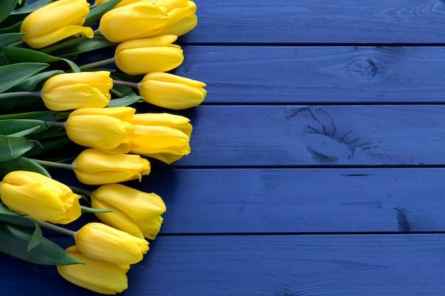 木製の背景に青いチューリップの花