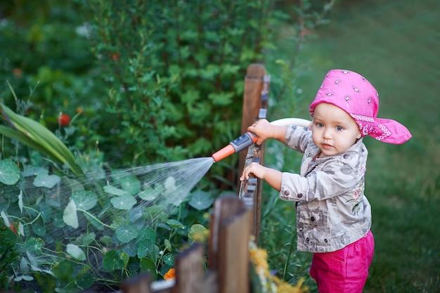 Маленькая девочка в розовых сапогах поливает цветы