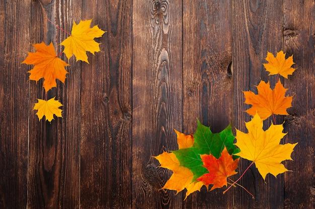 木製の背景に秋のカエデの葉のフレーム