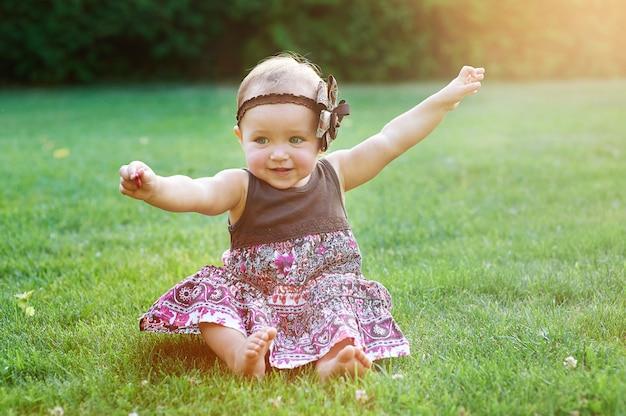 芝生の上の緑の草の上に座っている小さな女の子