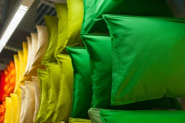 Много красочных подушек на полках