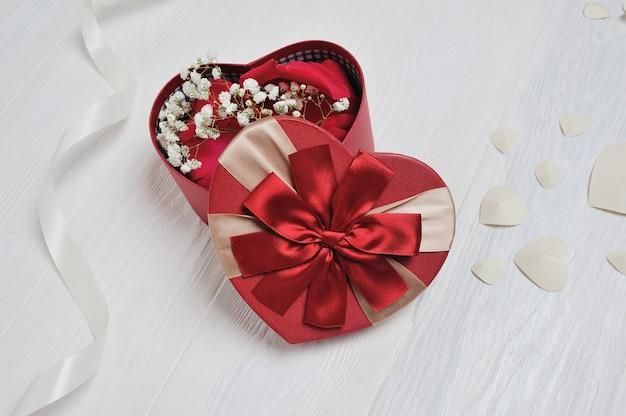 素朴なスタイルの聖バレンタインの日のハート型の赤いボックス