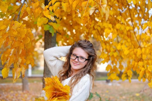 黄色の秋の花輪と美しい若い女性