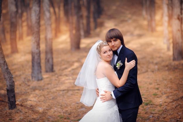 秋の森の中を歩く結婚式で新郎新婦