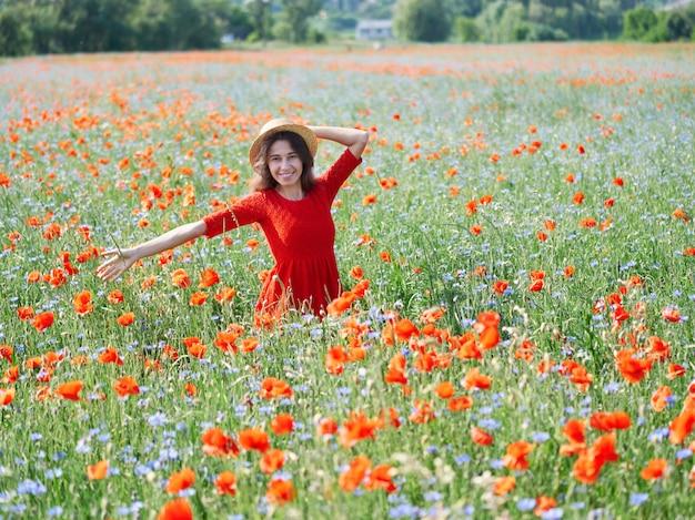 ケシの花のフィールドに麦わら帽子で素敵な若い女性