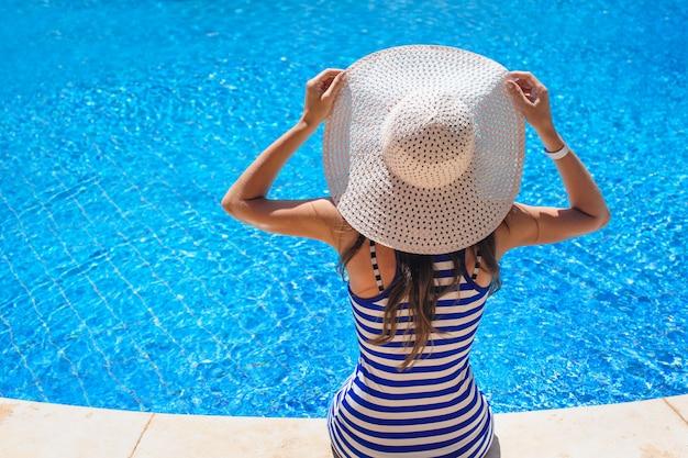 スイミングプールの端に座っている帽子で美しい女性