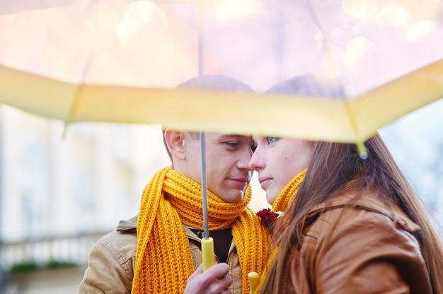 雨の中で傘の下で美しい若い愛情のあるカップル