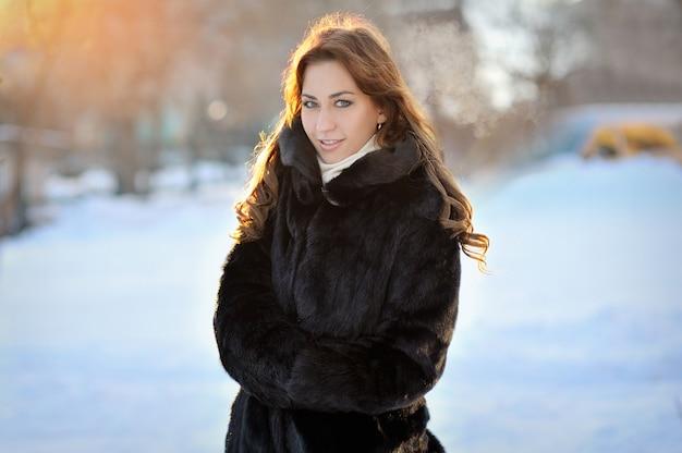 Красивая девушка в коричневом зимнем пальто на улице