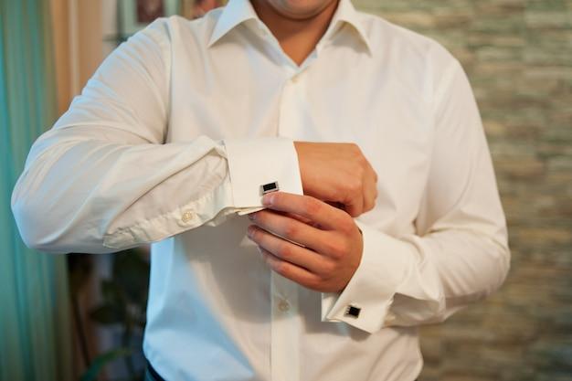 男はフレンチカフス袖の豪華な白いシャツにカフスを着ています。
