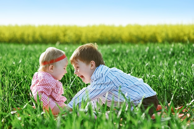Маленькие дети мальчик и девочка играют на зеленой траве