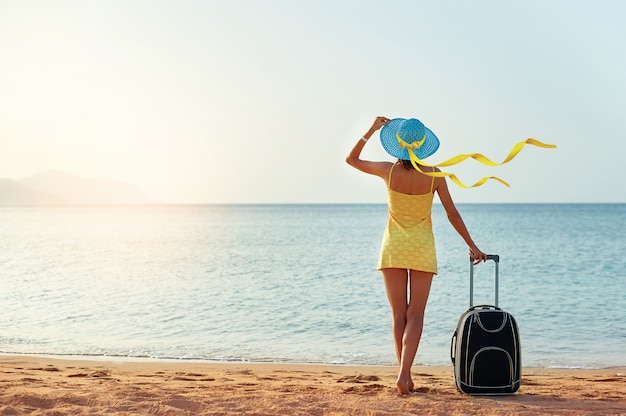 Красивая молодая женщина в шляпе стоит с чемоданом на фоне прекрасного моря
