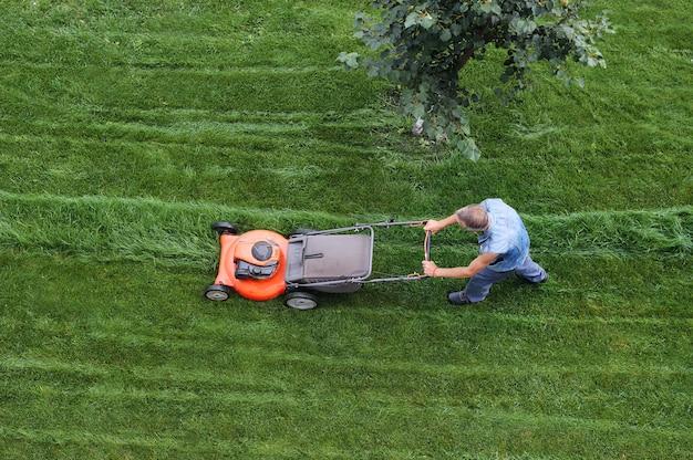男は芝生を切る。芝刈り。緑の芝生の空撮芝刈り機