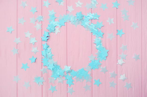 ラウンドフレームとピンクの木製の背景に青い星の紙吹雪