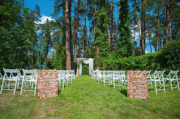 森の中での式のための白い椅子と結婚式のアーチ