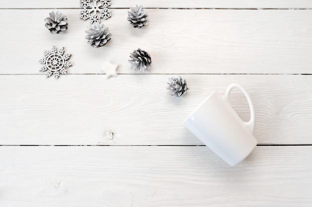 クリスマスの装飾の木製の背景にモックアップの白いマグカップ。平置き