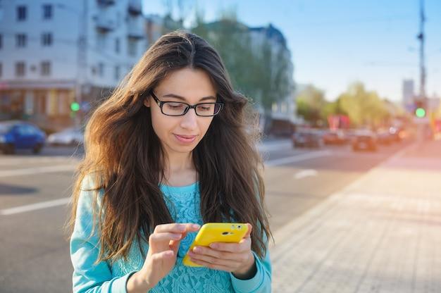 Красивая молодая женщина в очках с написанием смартфона