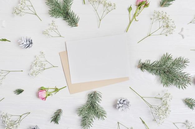 モックアップクリスマス組成。クリスマスカードと花、松ぼっくり