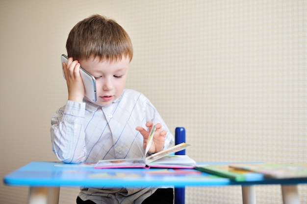 小さな男の子は学校の机に座って、電話で話す