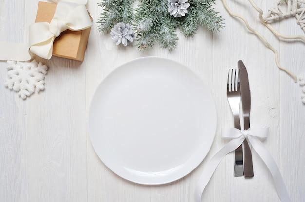 白い木製のテーブルのクリスマステーブルの設定。クリスマスカード