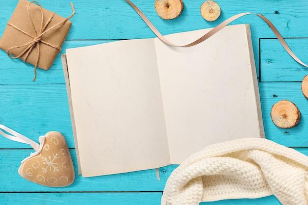 空白の開いたメモ帳、青緑色の木製のクリスマスプレゼントのモックアップします。
