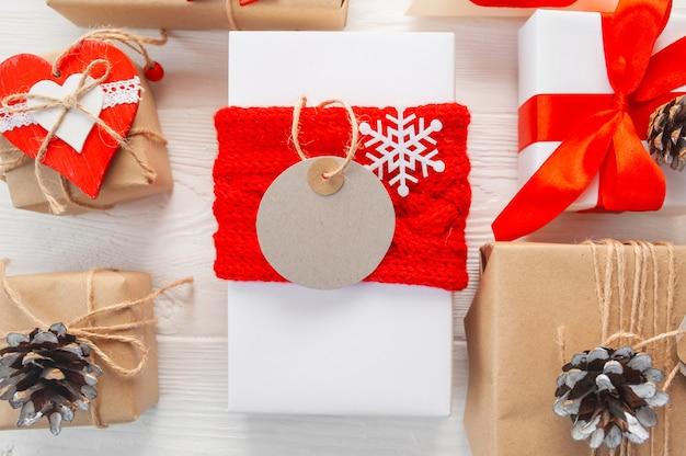 Макет рождественских крафт подарочных коробок с биркой на деревянной