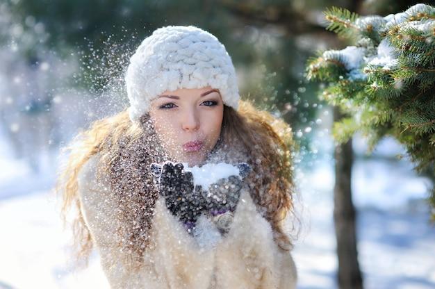 Девушка играет со снегом в парке