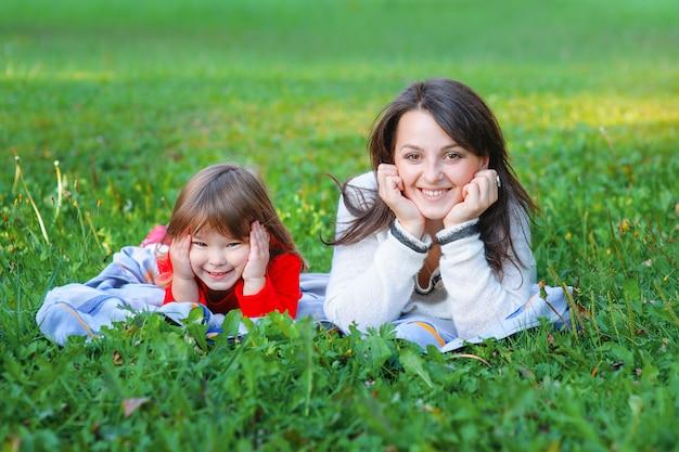 Счастливая мать и дочь лежат на траве в парке