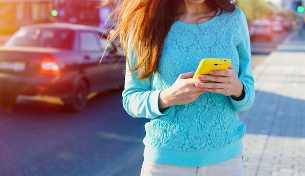通りで電話のテキストメッセージを持つ女性