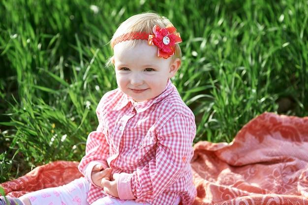 Маленькая девочка сидит на одеяле в летнем поле