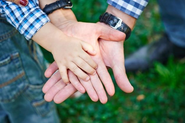 Мама и папа держат ребенка за руку