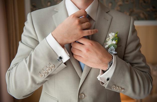 新郎はネクタイをまっすぐにセットします