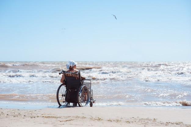 Вид сзади женщина-инвалид, сидя на инвалидной коляске на пляже в солнечный день