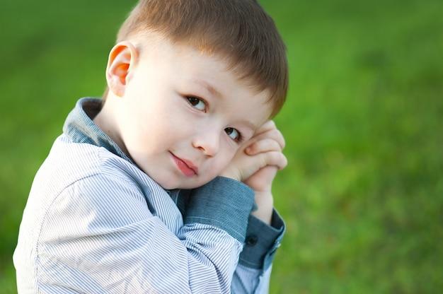 かわいい男の子は緑の芝生に座っています。彼は待っています。子供たちの幸せ