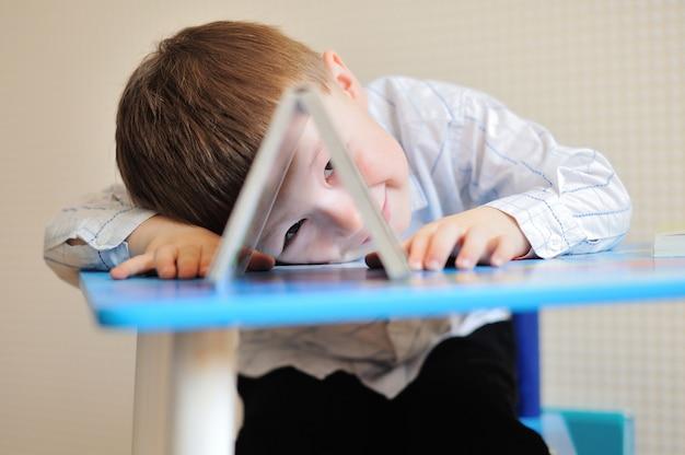 Молодой школьник играет с книгами и улыбается, как он сидит за столом в классе