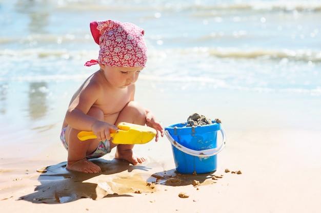 小さな女の子は海で青いバケツで遊んでいます。