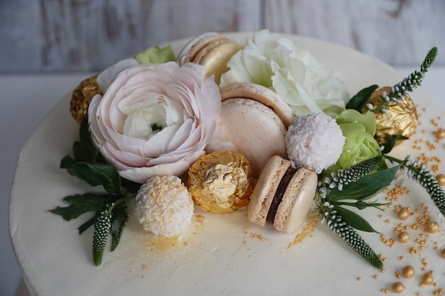 金色の花飾りが施された家族のベーカリーのおいしい、美しい結婚式のデザートをクローズアップ