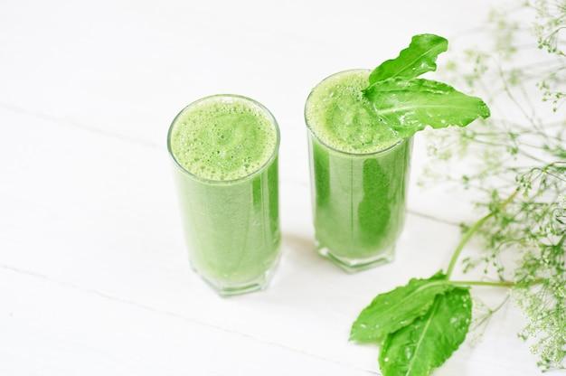 Смешанный зеленый коктейль с ингредиентами или коктейлем