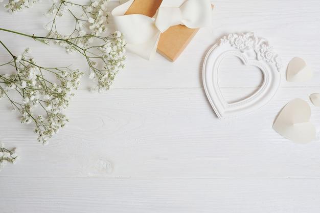 Макет композиция из белых цветов в деревенском стиле, сердца любви и подарок. валентинка