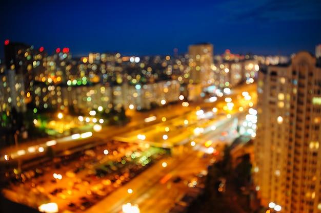 ぼやけた多重夜景の上から夜の街の景色