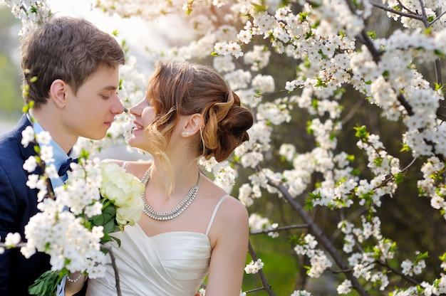 花の咲く春の庭を歩く新郎新婦。バレンタインデート