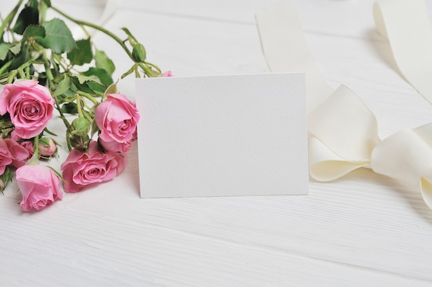 ピンクのバラと紙で作られたモックアップ白い折り紙ハート。バレンタインデートカード