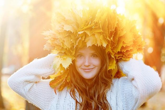 公園を歩いて黄色の葉の花輪を持つ幸せな若い女
