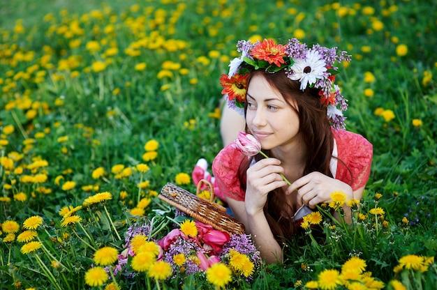 牧草地の草の上に横たわる花輪で美しい女性