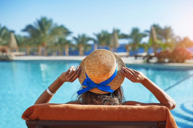 スイミングプールでサンラウンジャーに座っている若い女性