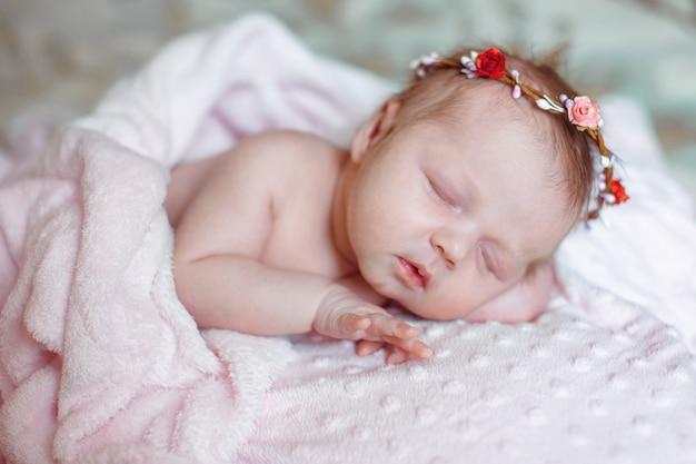 Прекрасная новорожденная девушка спит на розовом одеяле