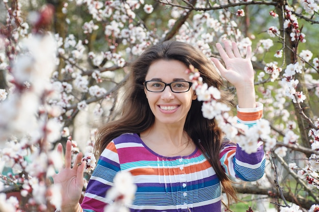 桜の木の中で手を振って幸せな若い女