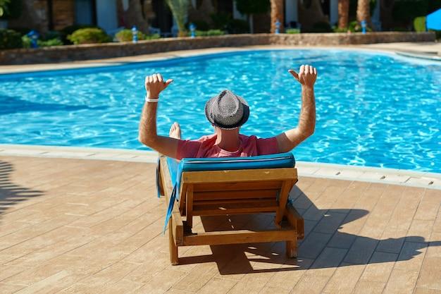 Молодой человек в шляпе и розовой футболке лежит на шезлонге у бассейна
