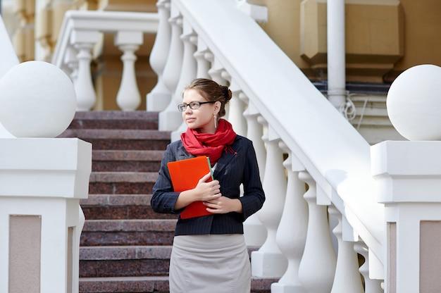 若いビジネス女性が事務所ビルに対してフォルダーを手で保持します。